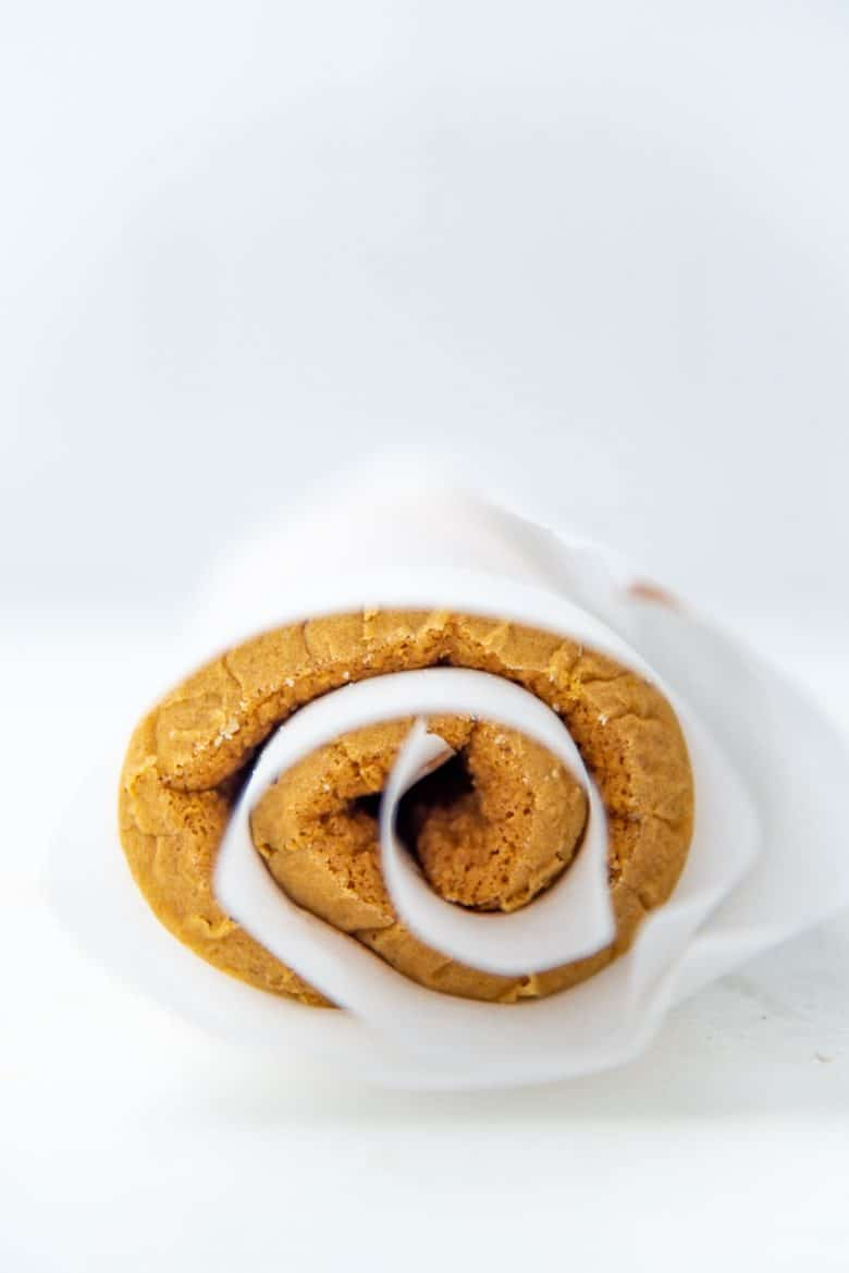 Rolled up pumpkin swiss roll in parchment paper cooling down