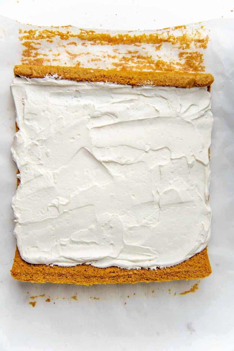 Un rolled pumpkin cake, with cream cheese whipped cream spread evenly