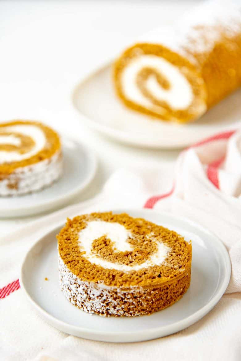 Slices of the pumpkin cake roll on small white plates