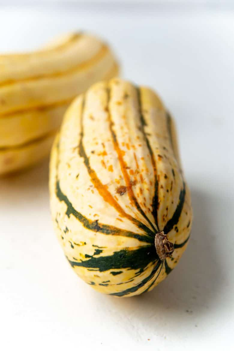 A close up of delicata squash showing green and orange ridges