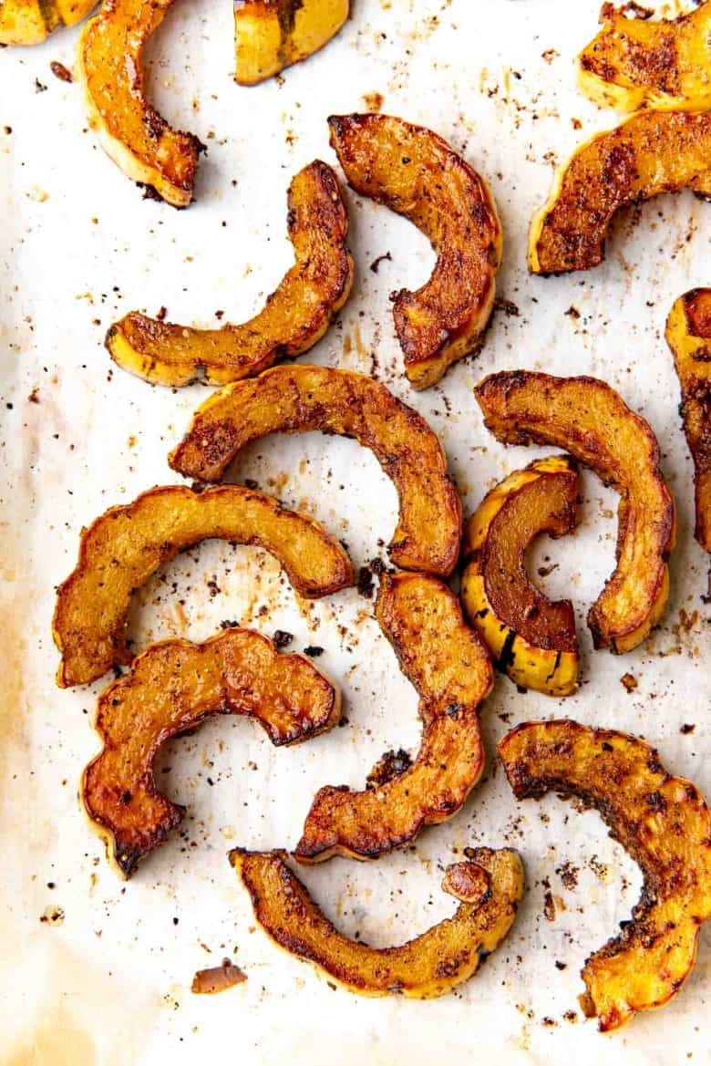 Overhead view of roasted delicata squash half rings on a baking tray