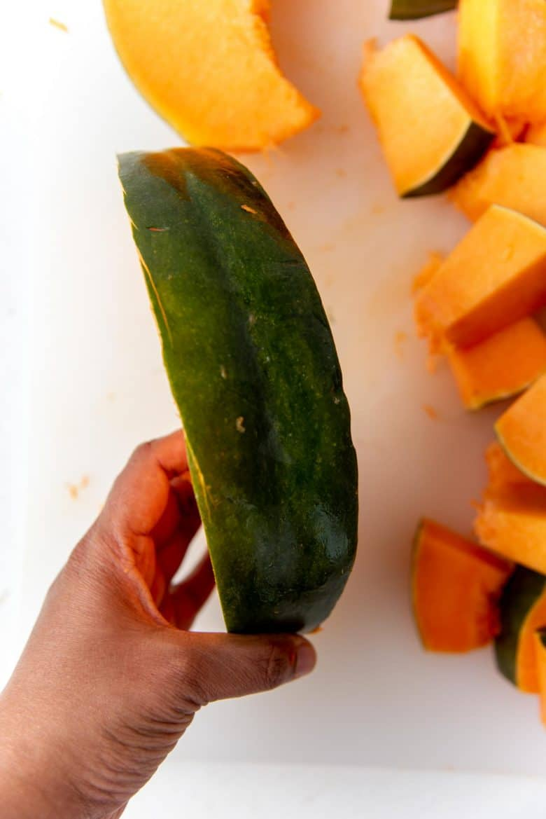 An image holding up a wedge of pumpkin to show thickness