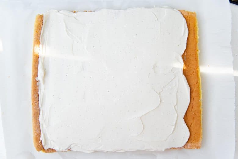 Spreading a layer of whipped cream on the cake
