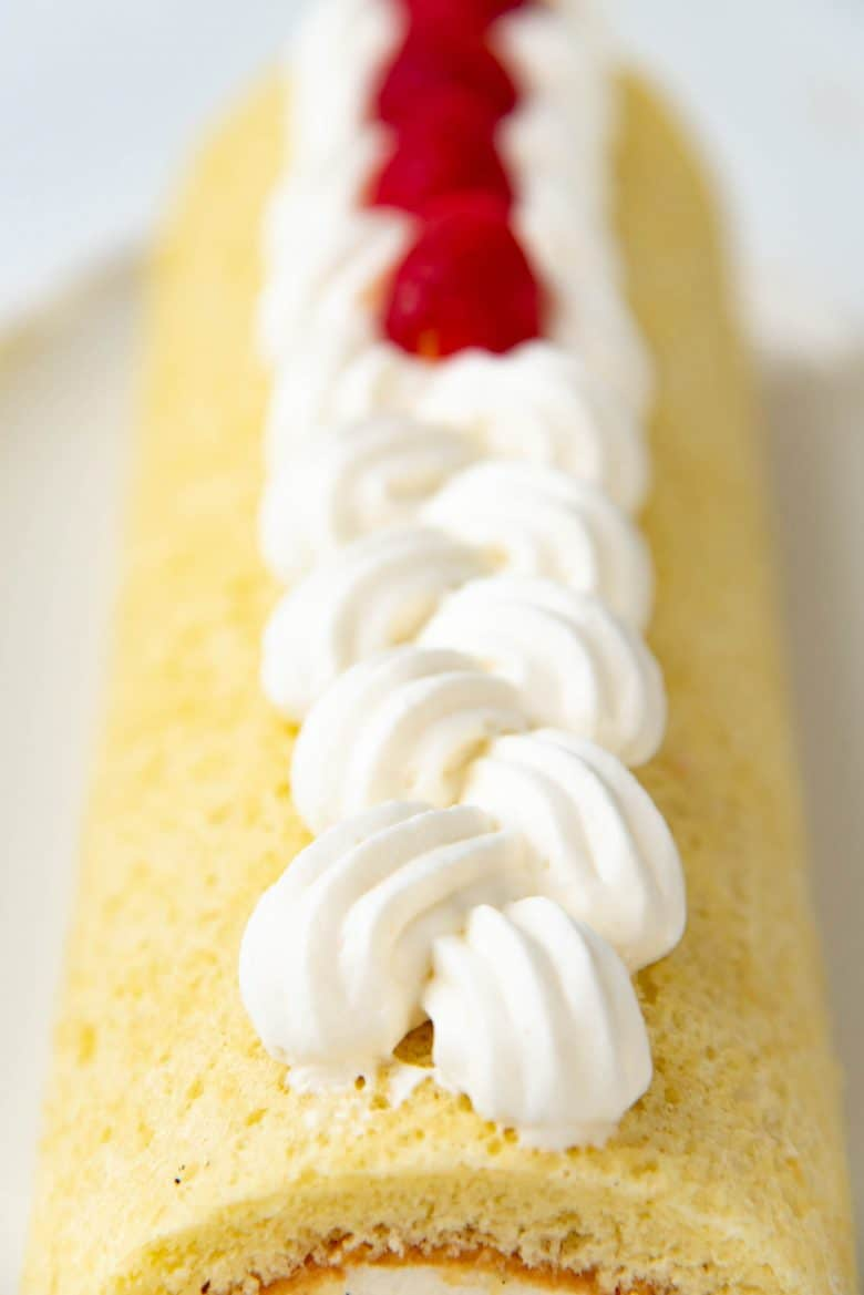 A close up of the piped border ontop of the vanilla swiss roll cake