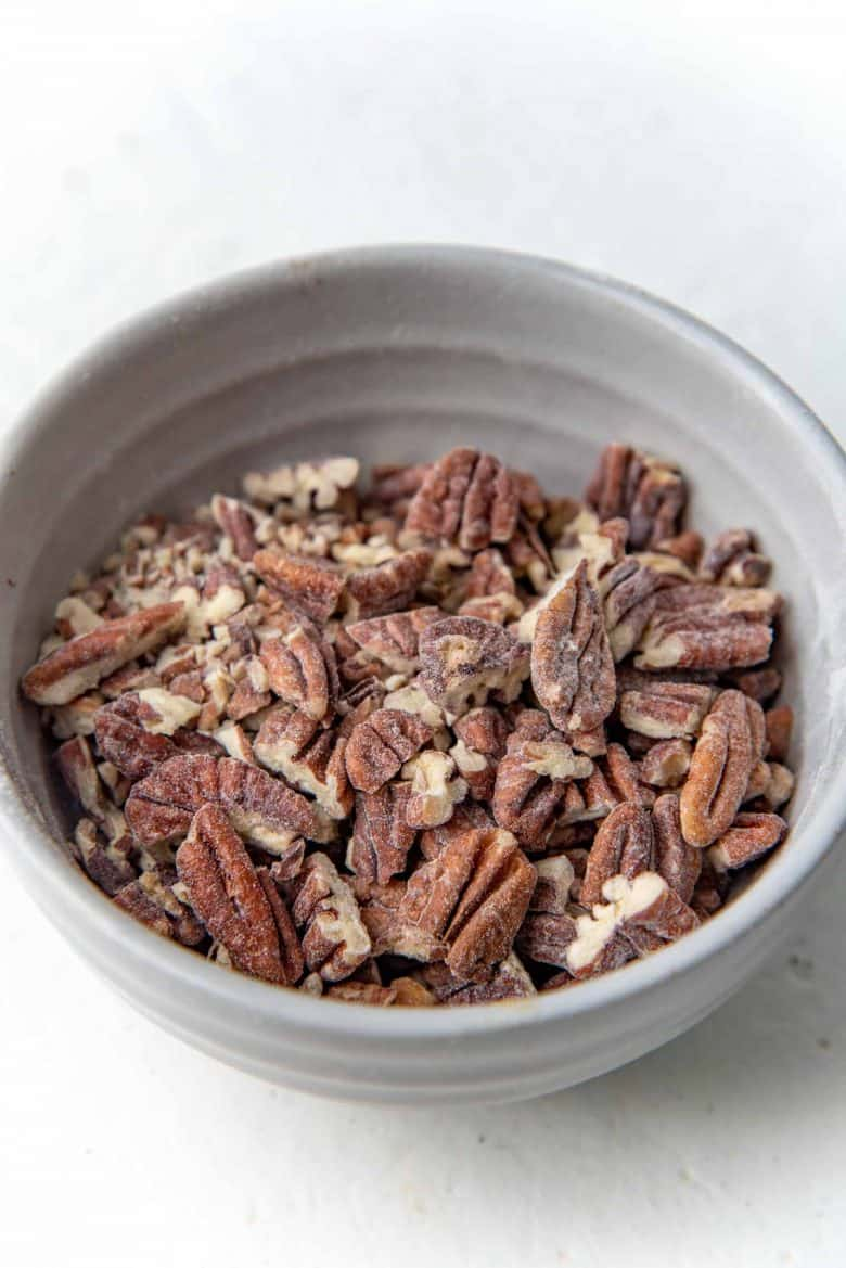 Flour dusted chopped pecans in a bowl