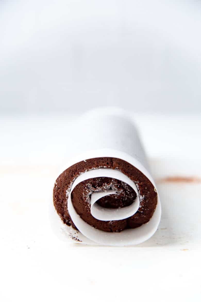 Swiss roll cake rolled up in parchment paper without filling