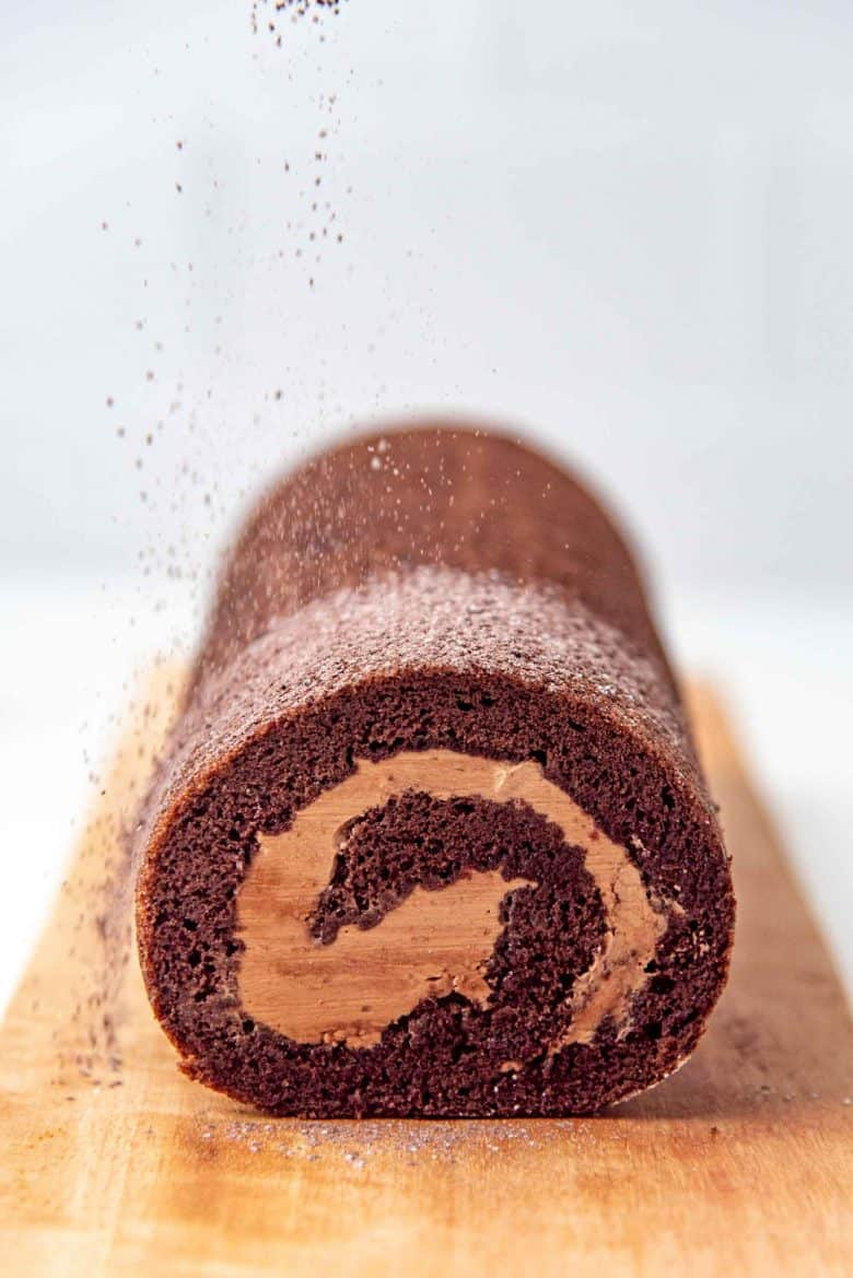 Sprinkling confectioners sugar ontop of the chocolate roll cake