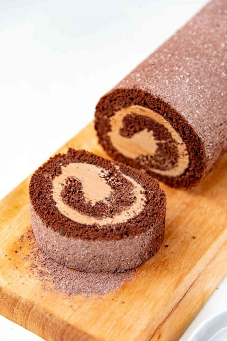 Chocolate swiss roll on a brown serving platter, with a slice cut