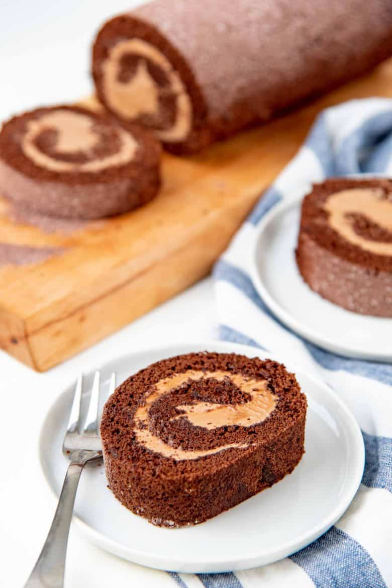 Swiss roll slices on plates, and the whole cake in the background