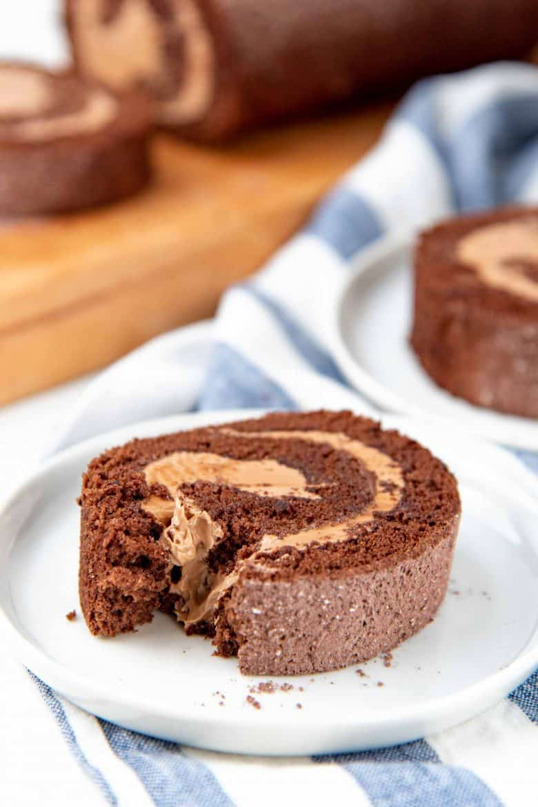 A slice of chocolate swiss roll on a small plate, with a small piece taken out