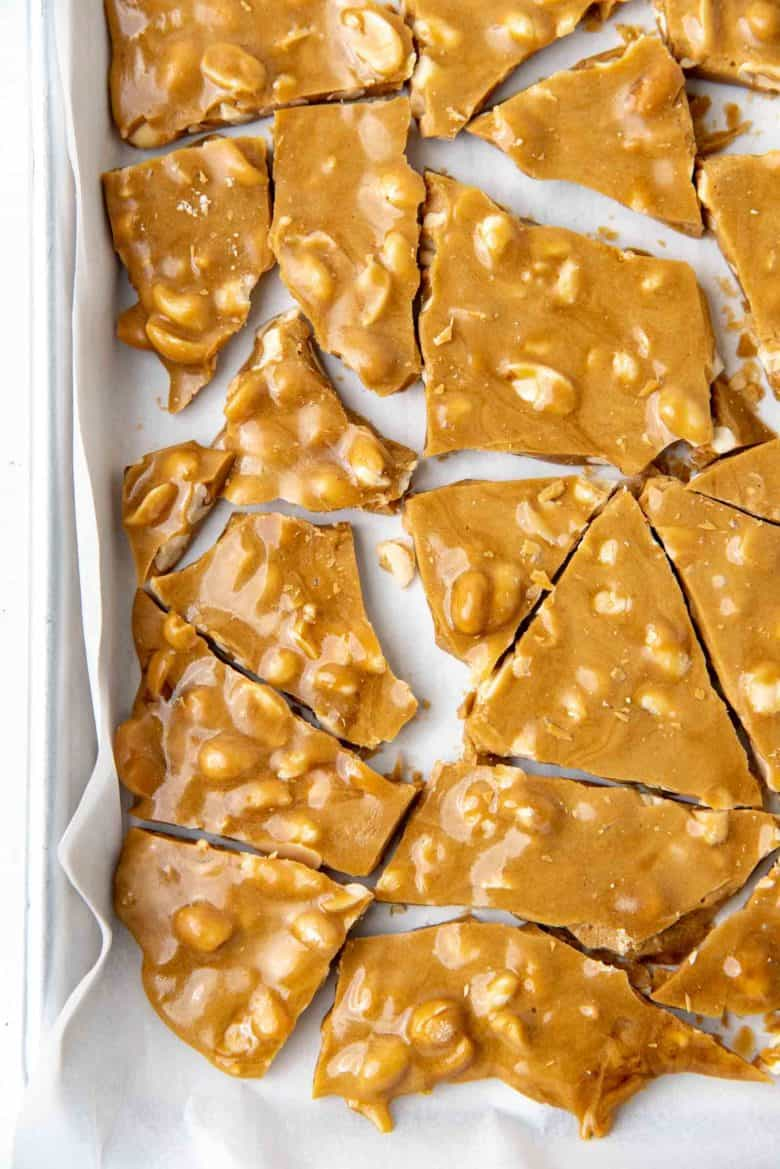 A close up of the cracked nut brittle on the baking sheet