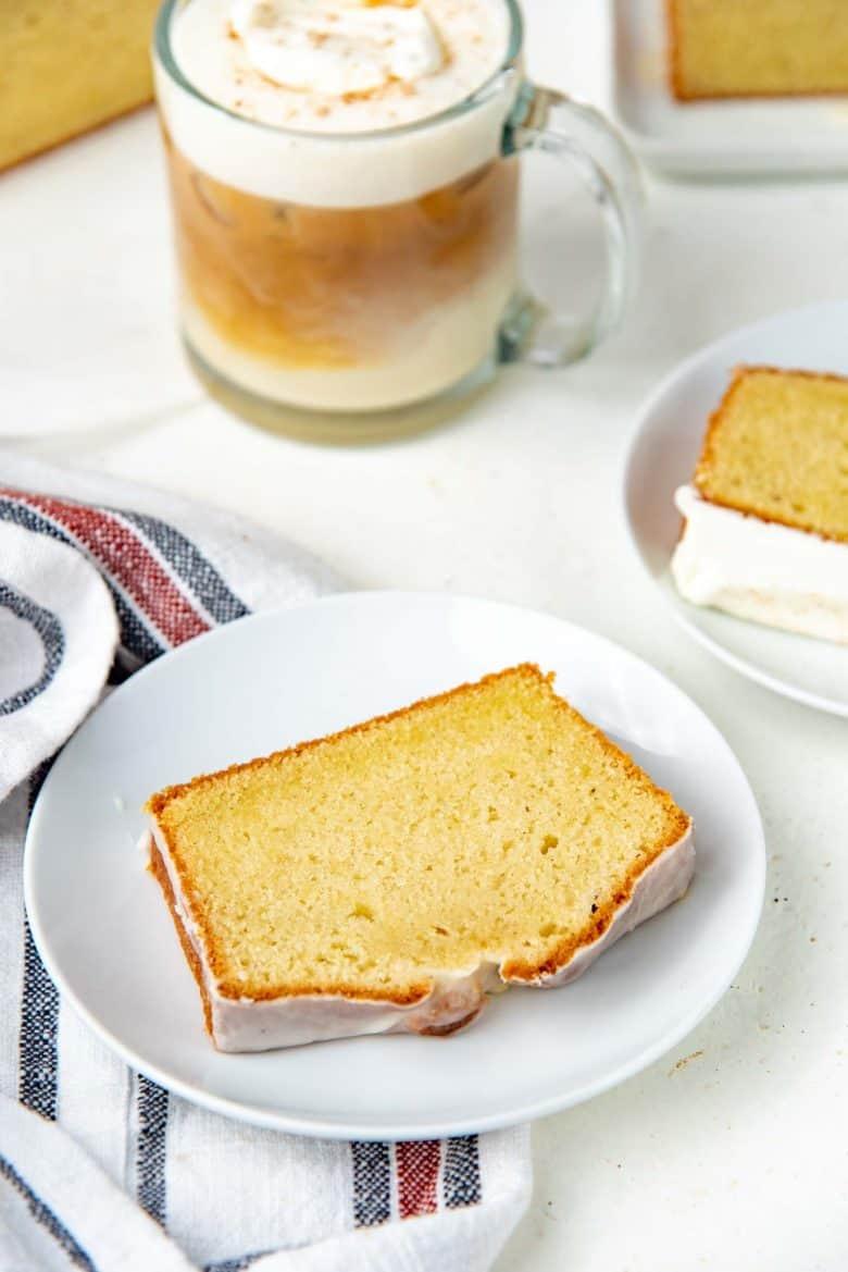 Glazed eggnog cake slice on a plate, with eggnog latte in the background