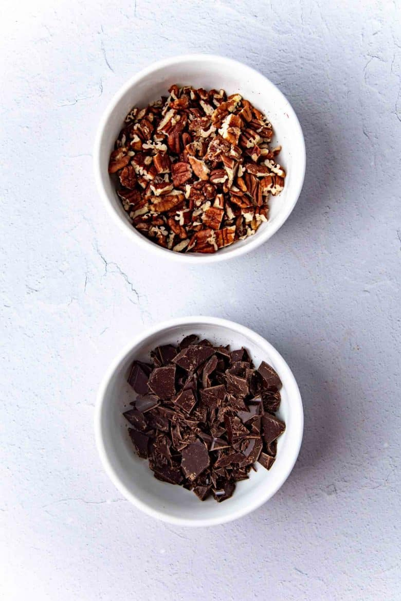 Chopped chocolate and chopped pecans in a bowl