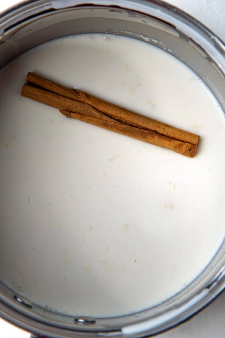 Milk in a saucepan with a cinnamon stick