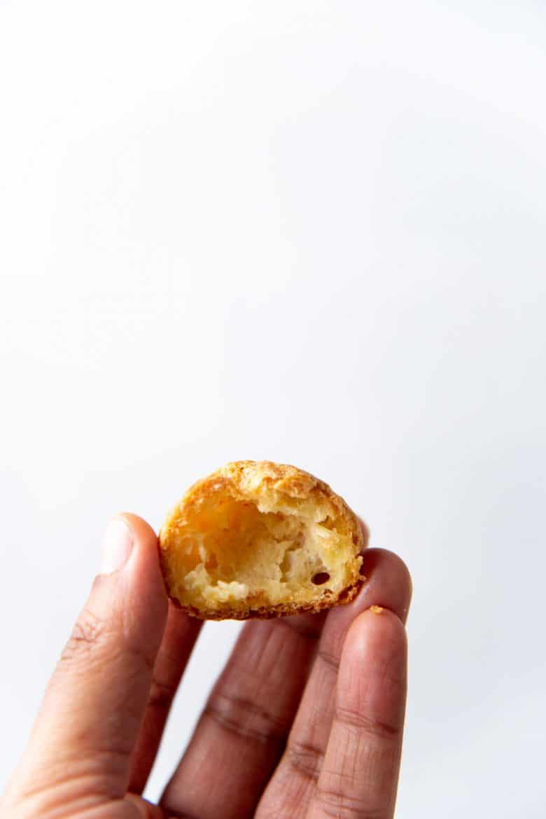 An empty choux puff cut in half to show the center
