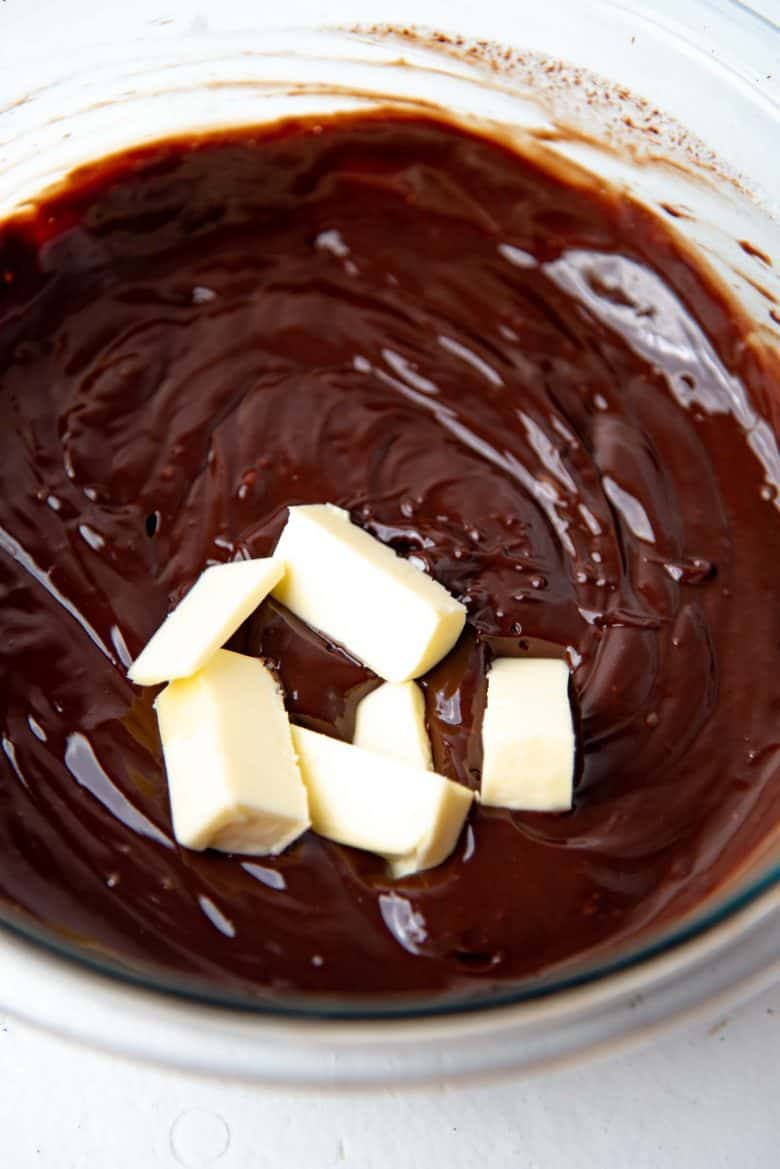 Adding the softened butter to the chocolate ganache mixture
