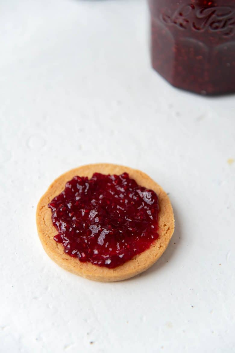 Spreading a dollop of the jam on a linzer cookie