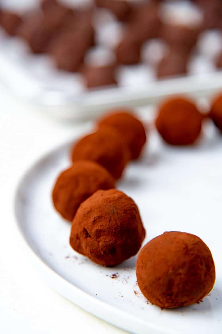 Cocoa powder coated truffles on a white plate