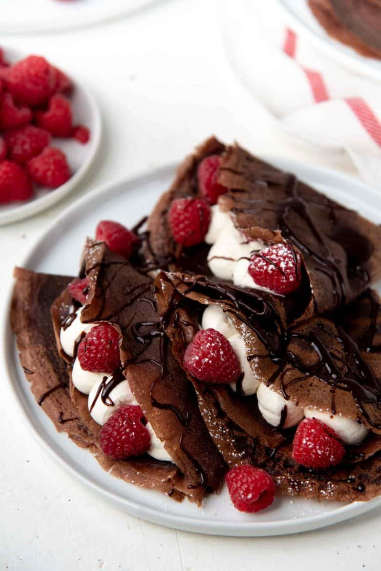Chocolate Crepes folded over and filled with cream and raspberries