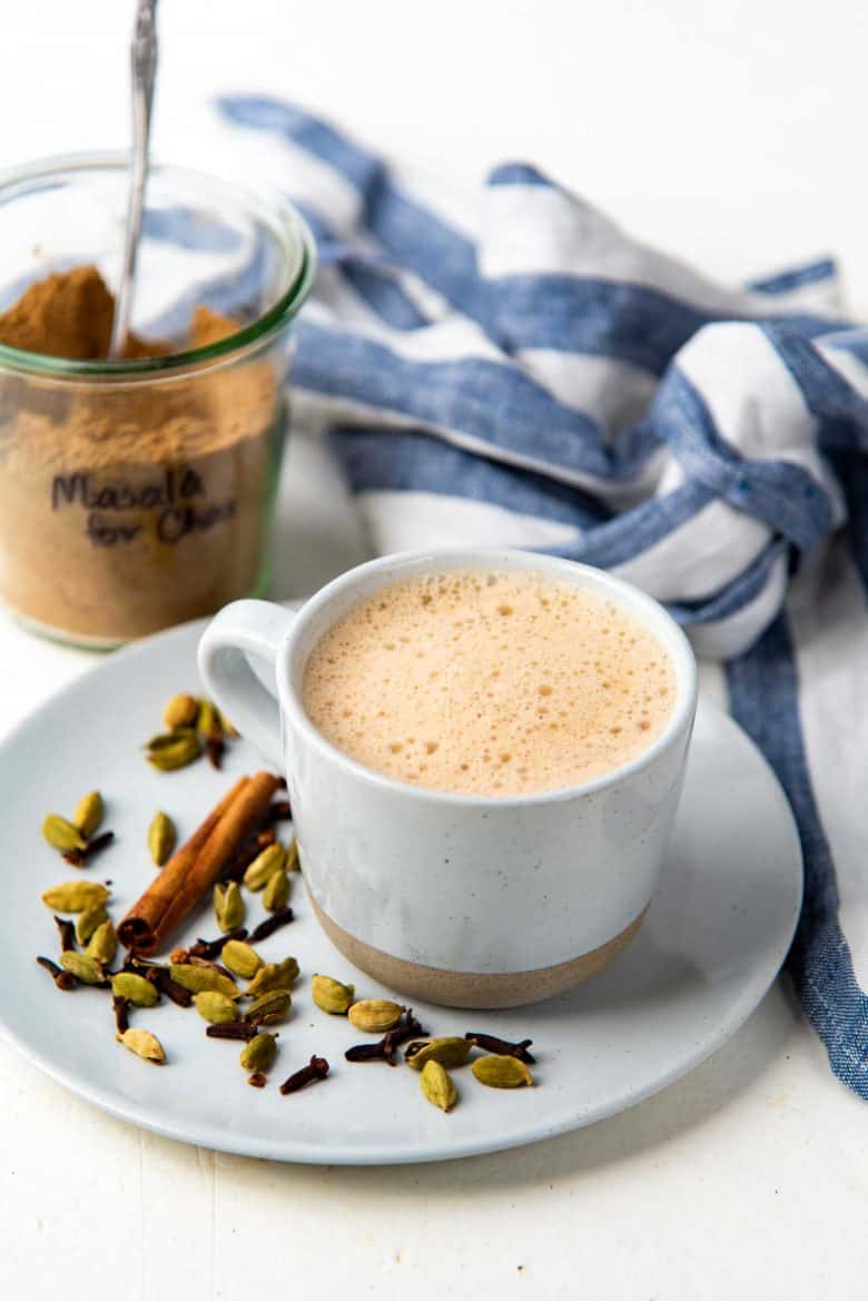 Masala Chai served in a mug with the spice mix in a jar
