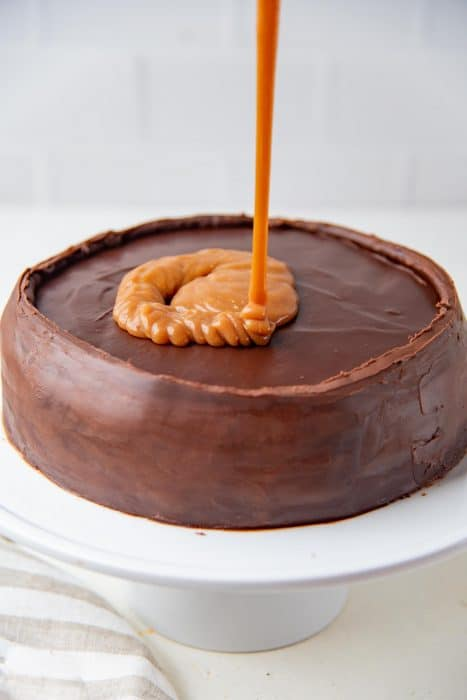 Pouring salted caramel sauce on top of the chocolate ganache on the cake