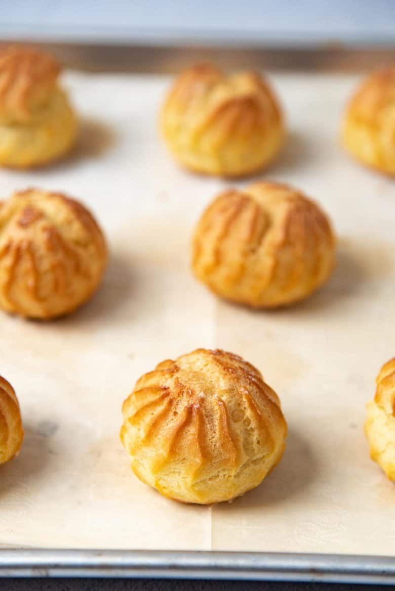 Freshly baked choux pastry on a baking tray