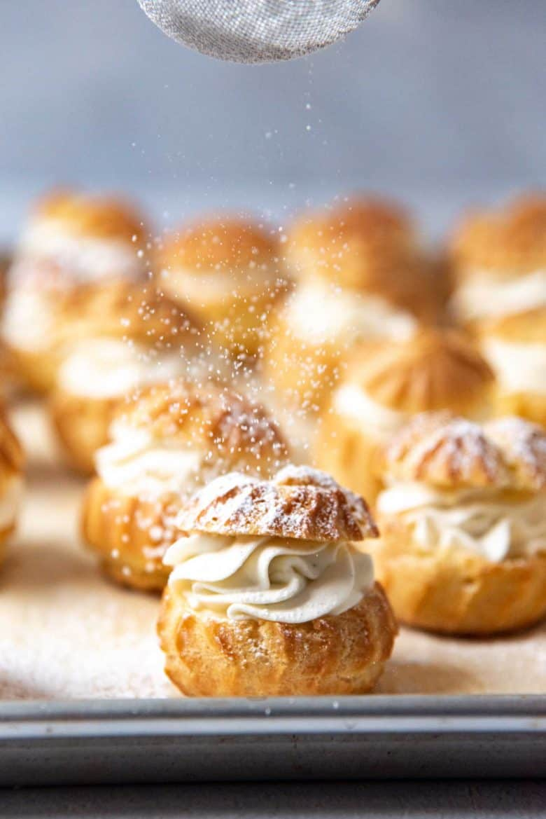 Cream puffs on a tray, with confectioner's sugar being dusted on top
