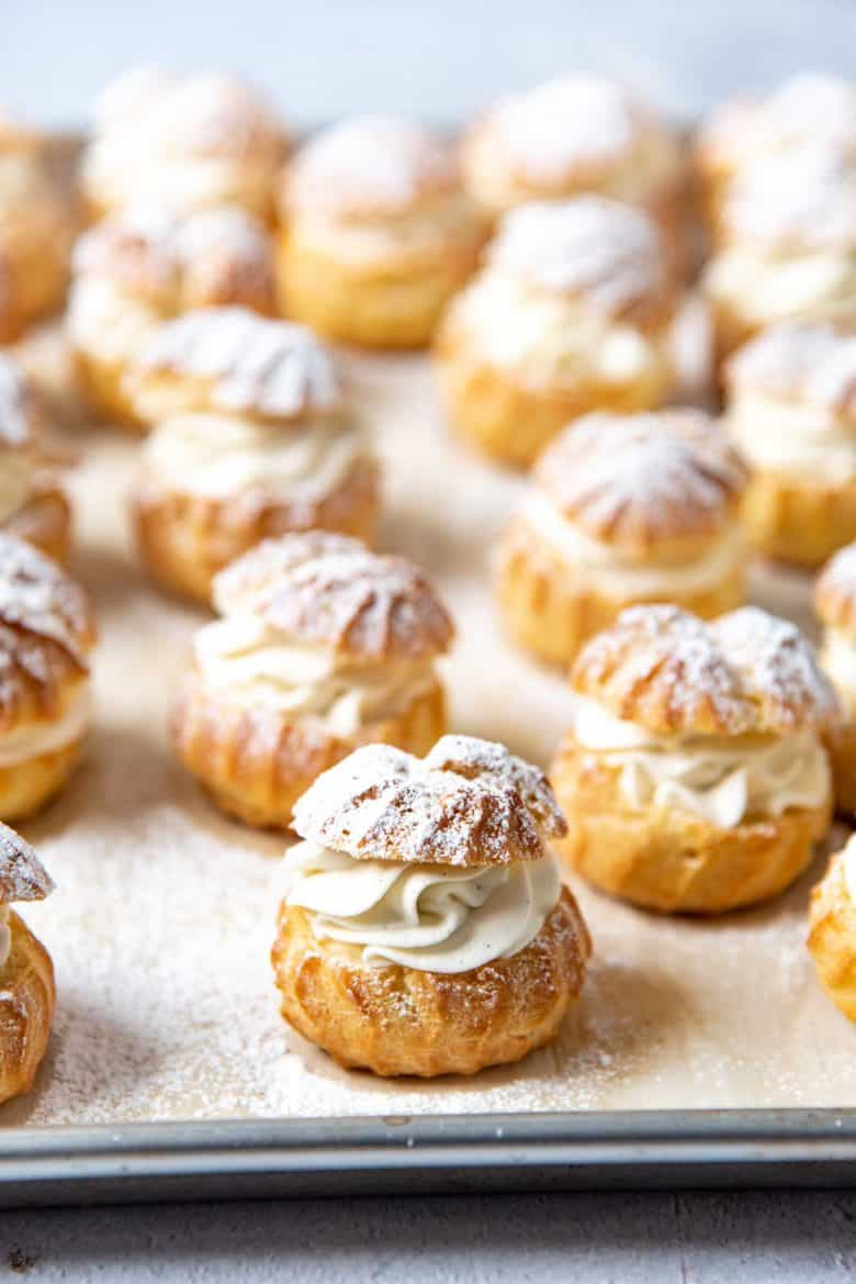 Filled choux puffs dusted with confectioner's sugar on a baking tray