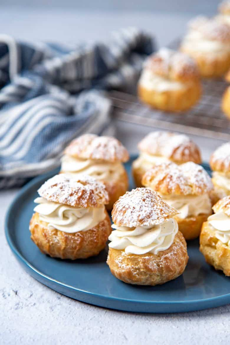 Chantilly cream filled choux pastry placed on a blue plate