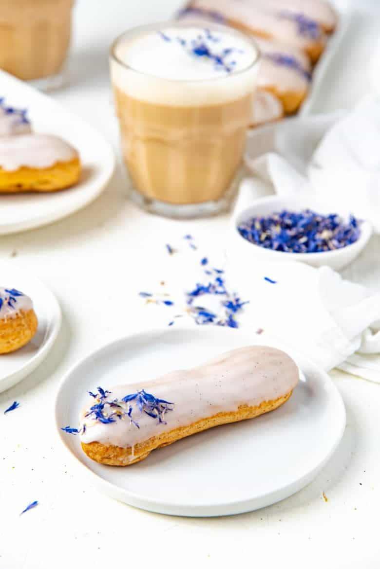 Earl grey eclair served on a white plate with earl grey latte in the background