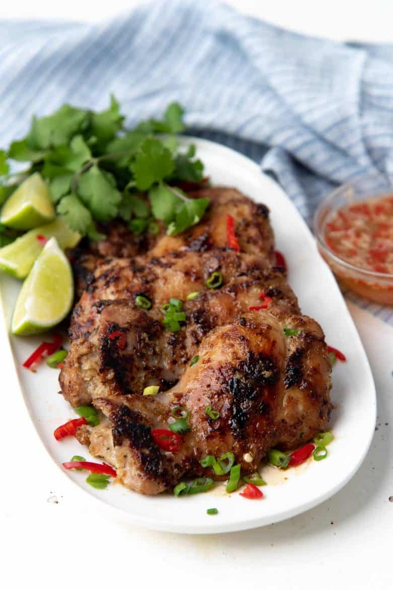 Grilled chicken thighs on a white platter with cilantro and lime slices
