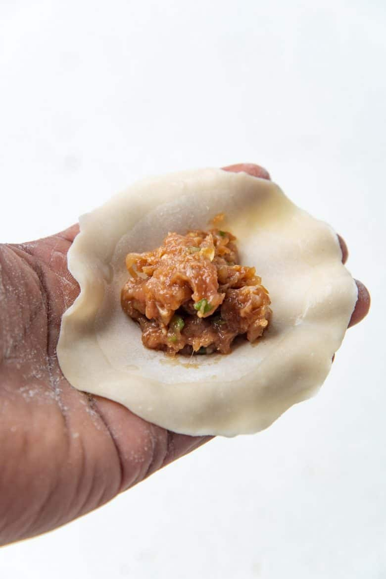 Placing chicken dumpling filling in the middle of the wrapper