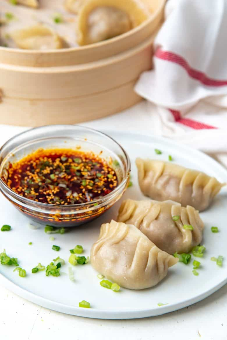 Close up of steamed chicken dumplings on a plate with spicy dipping sauce