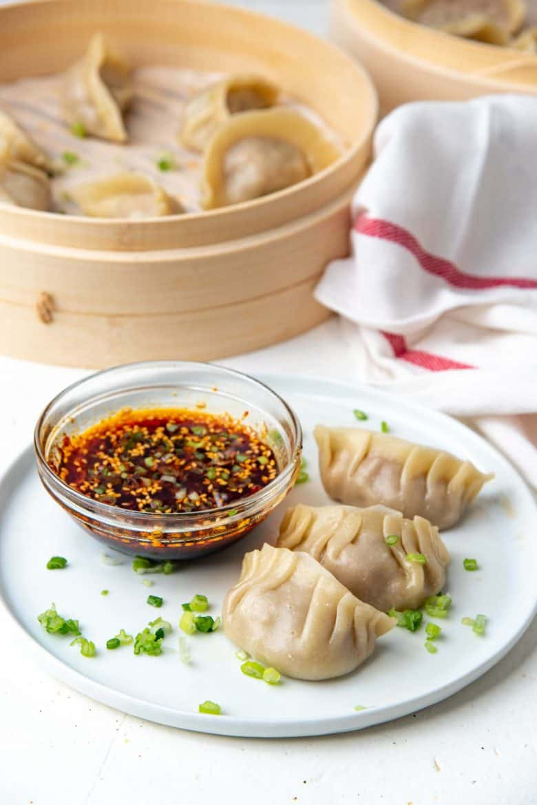 Dumplings served on a white plate with dipping sauce