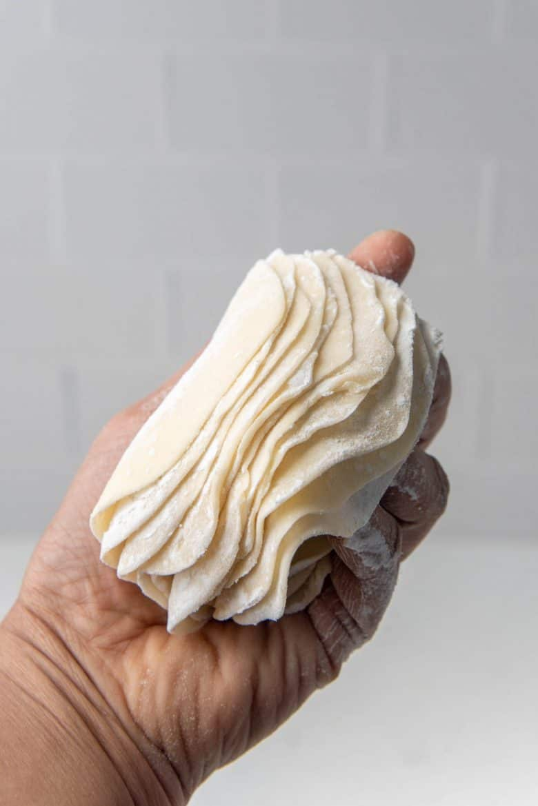 A stack of dumpling wrappers being held in a hand