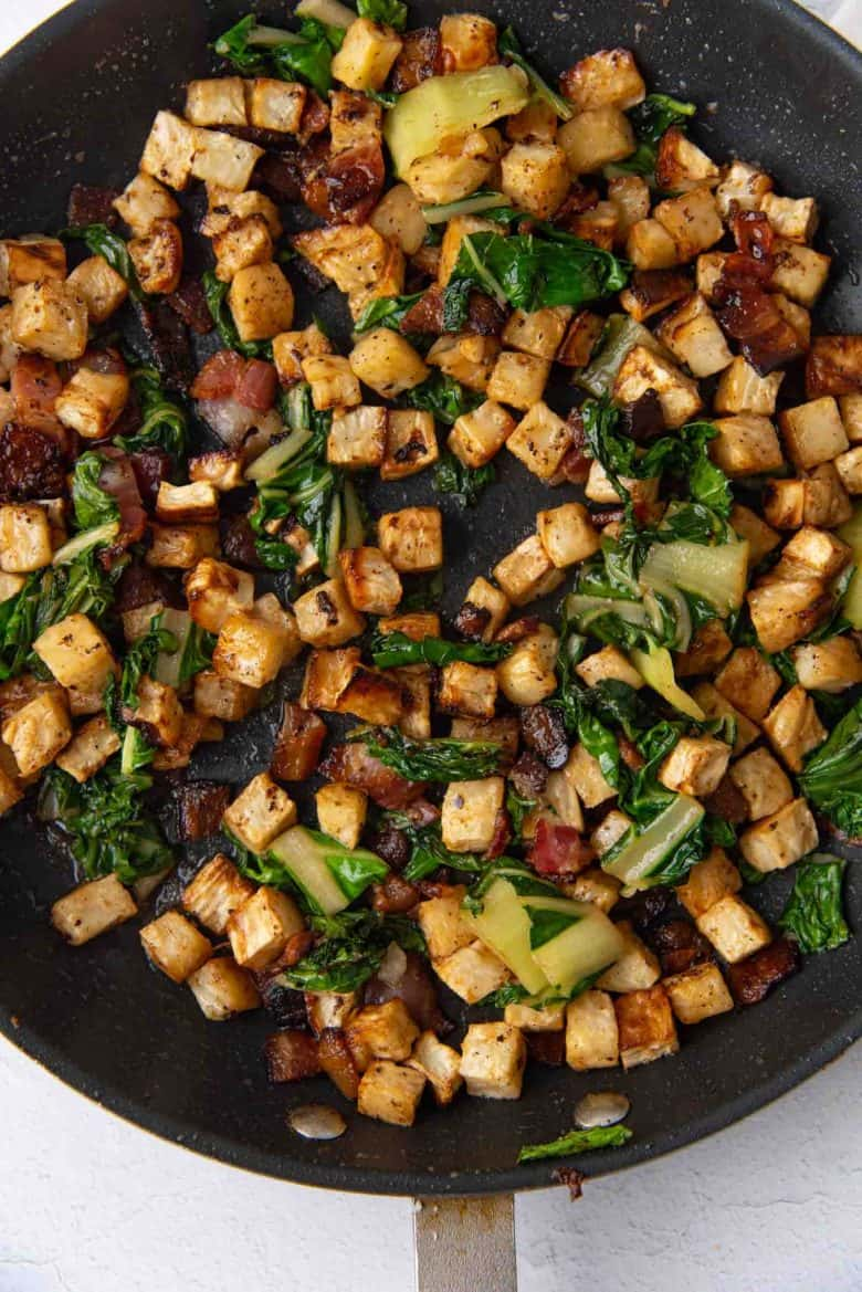 Celeriac hash tossed with swiss chard in a pan