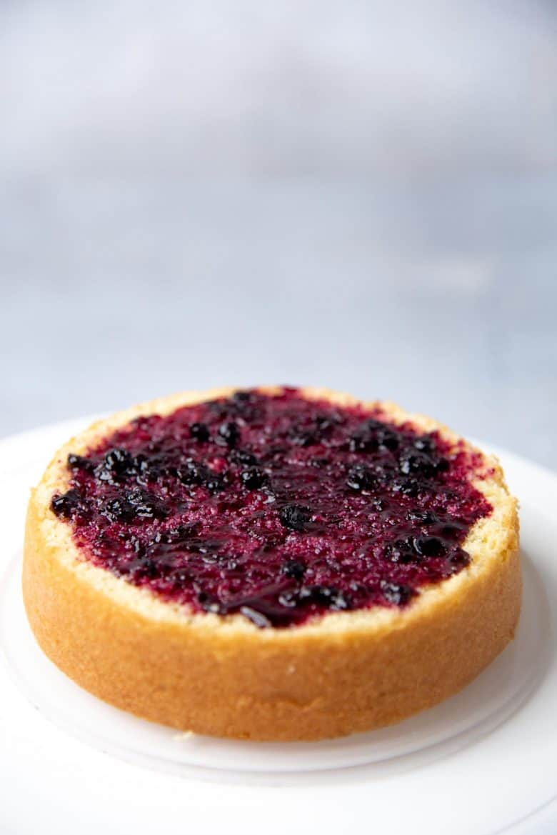 Spreading a layer of blueberry jam on the spiced cake layer