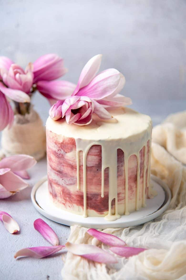 Ginger cardamom cake with rose buttercream served on a plate with magnolia flowers in the background