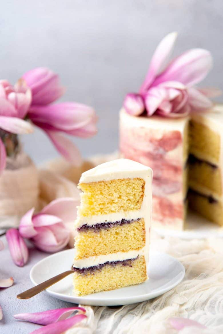 Slice of the ginger cardamom cake with rose buttercream with the whole cake in the background