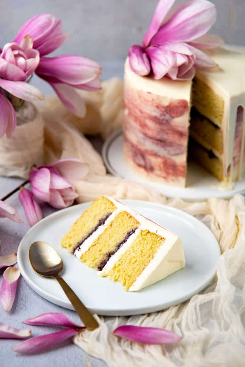 Slice of the ginger cardamom cake, showing the blueberry jam and rose buttercream filling