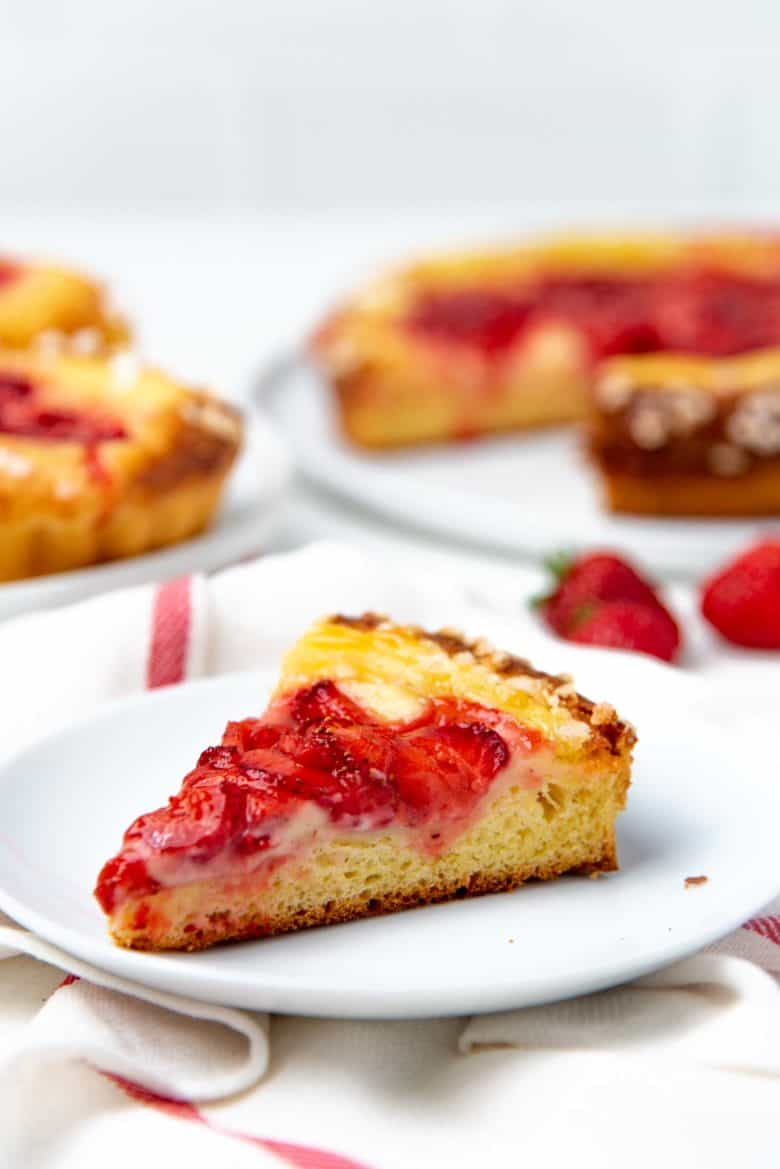 A slice from a large brioche tart served on a plate, with the custard and strawberry layers visible