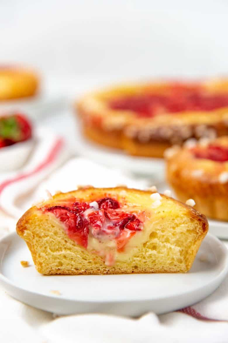 A cross section of the mini brioche tart, showing the layer of custard and strawberry.