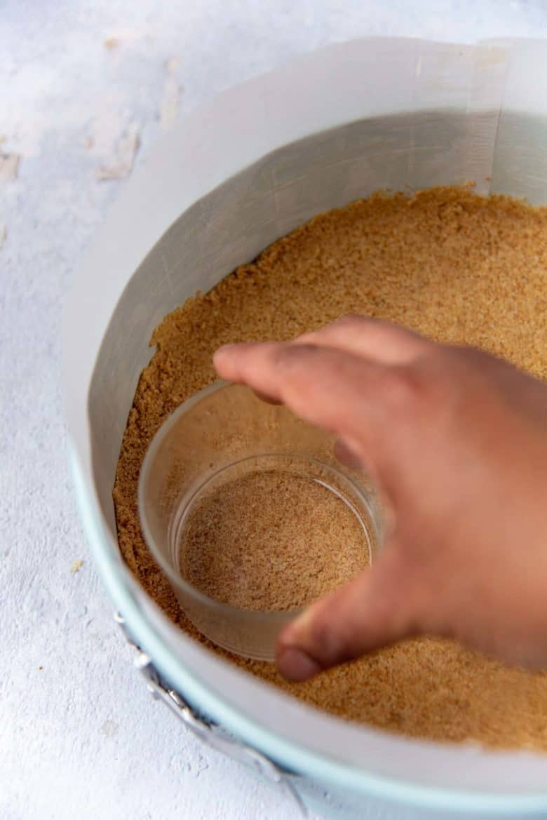 Pressing the graham cracker crumbs into the bottom of the pan