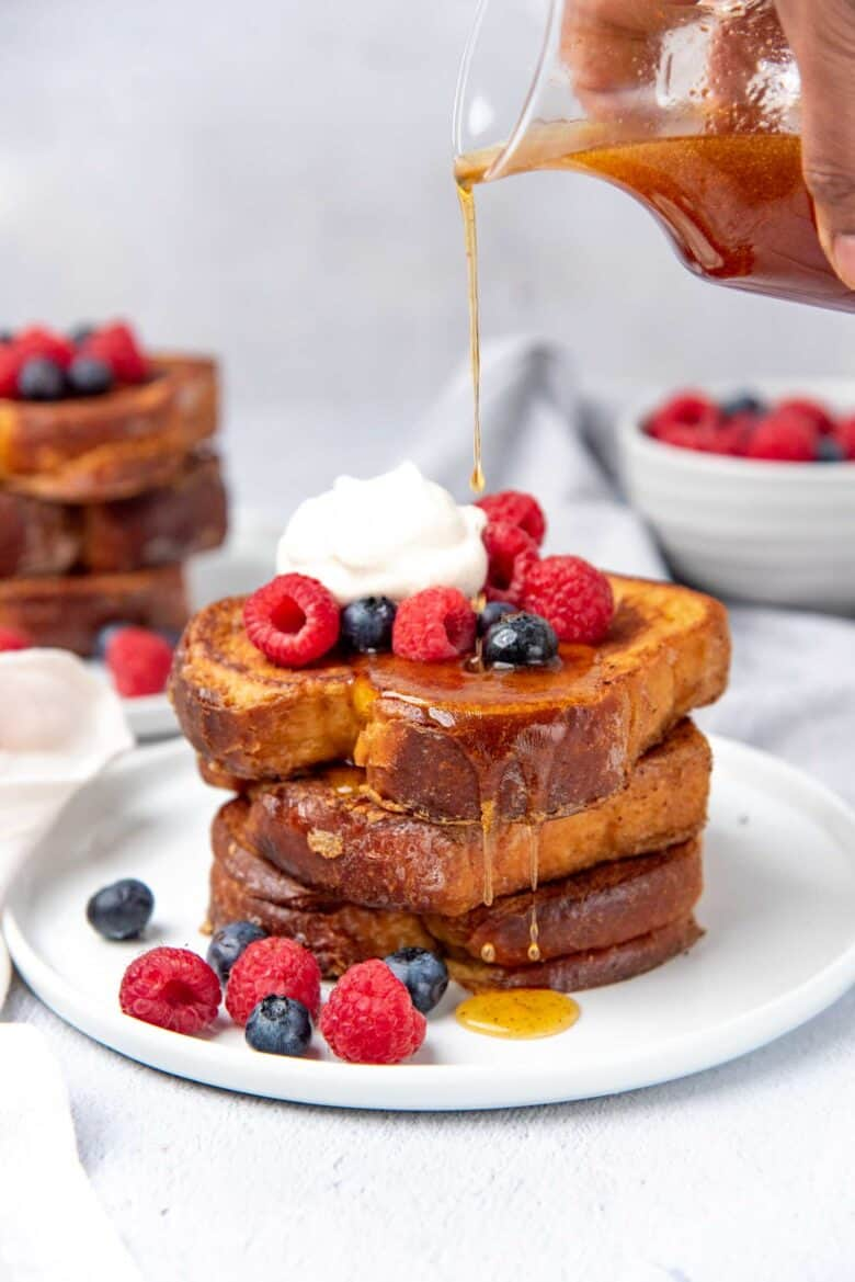 Pouring maple syrup over the stack of eggy bread