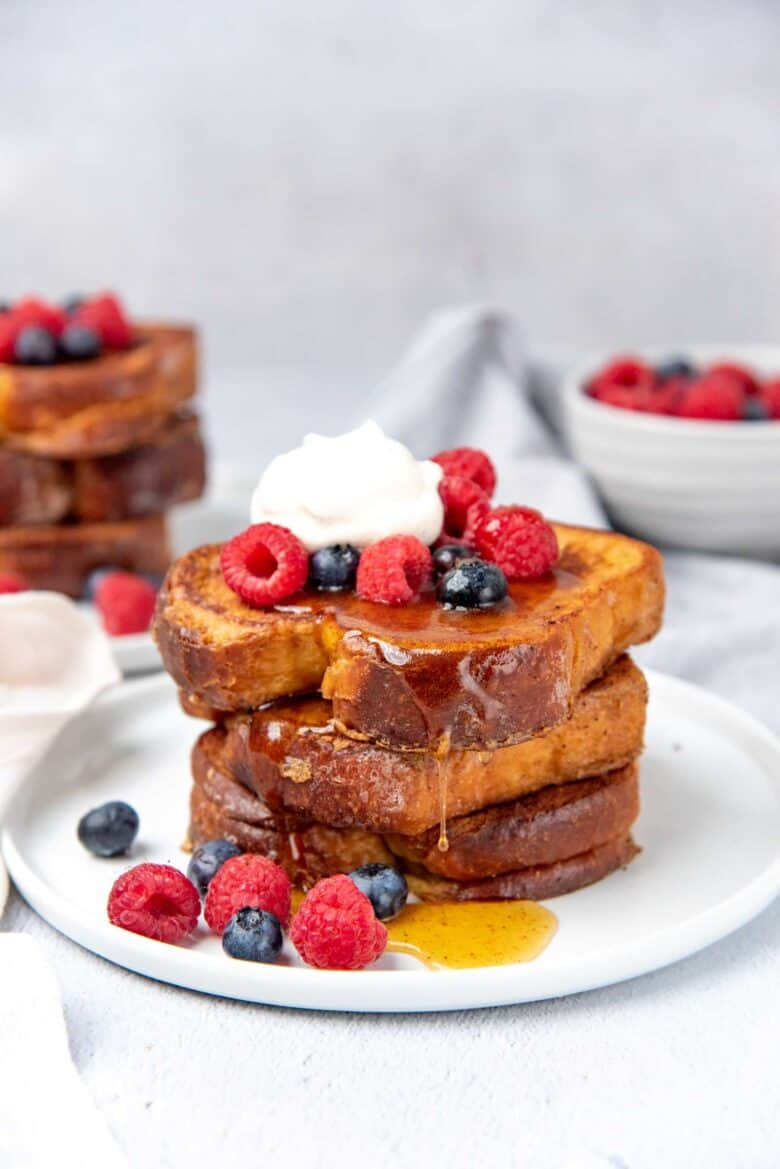 Stack of french toast on a white plate with fresh fruits and syrup