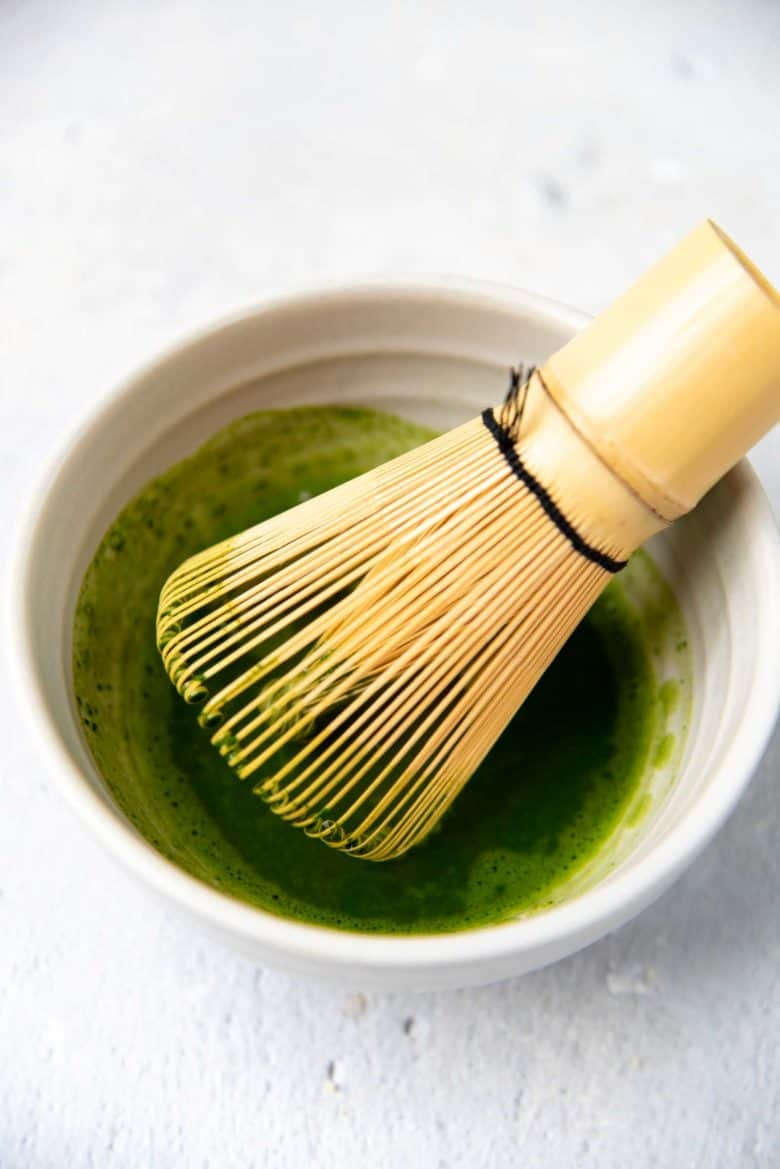 Whisking matcha with a bamboo whisk