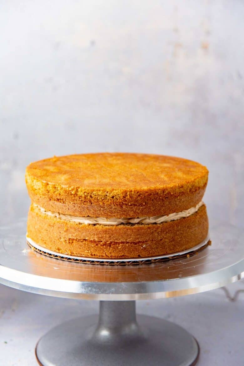 The second coffee flavored cake layer placed on top to assemble the cake