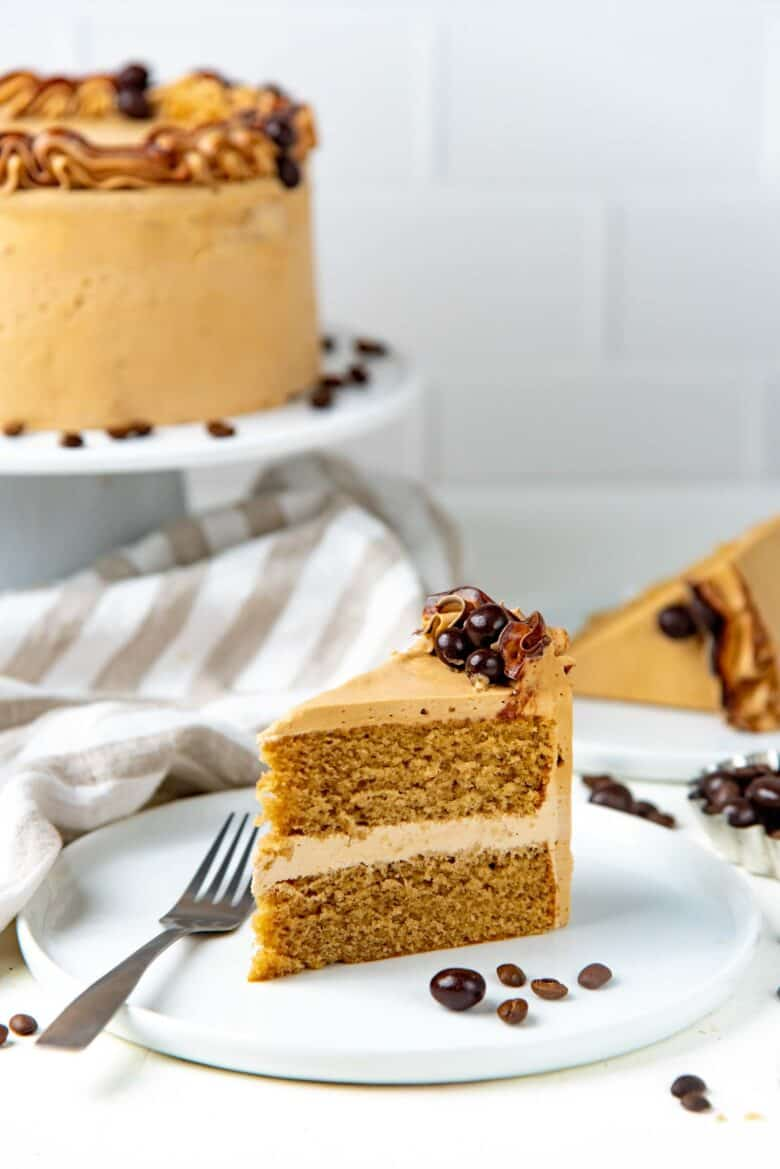 A slice of the coffee layer cake on a white plate with the whole cake in the background
