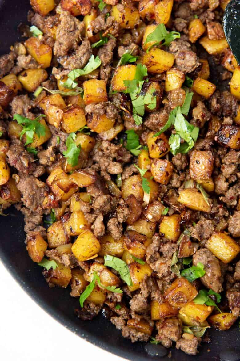 Curried potato hash with ground beef in a skillet