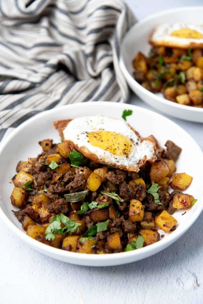 Breakfast home fries with curry flavors served with an egg